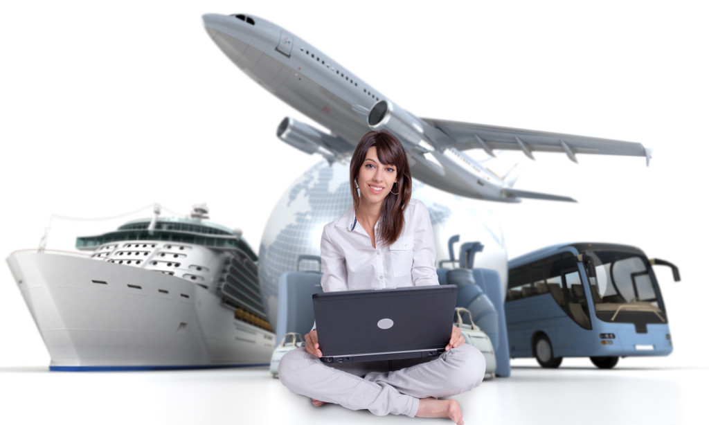 Young woman sitting on the floor with a laptop with an international tourism background