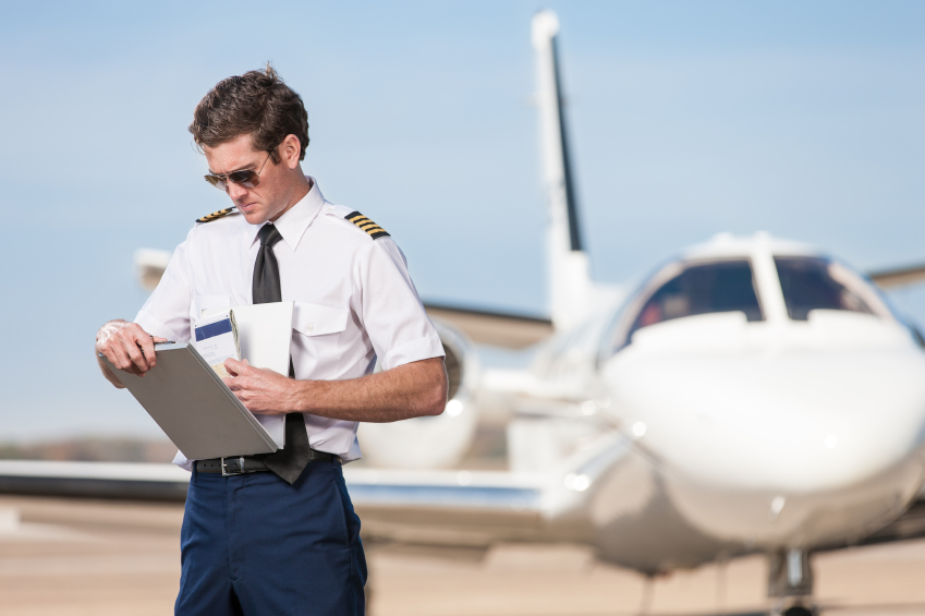 A male pilot stands outside of a corporate jet aircraft, reviewing a flight log book.